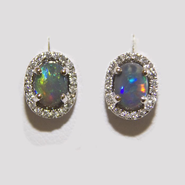 Black opal and diamond earrings in a classic design.  The Black Opals weigh .95 carats total, accented by .27 carats of fine white round brilliant cut diamonds, set in 14k white gold.