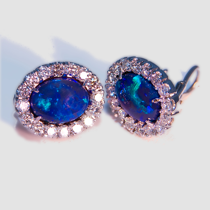 Black Opal and diamond earrings with a rare-matched pair of oval blue green Black Opals.  The Black Opals weigh 5.05 carats and are accented by 1.58 carats of fine white round brilliant cut diamonds. French backs are set in 18k white gold.