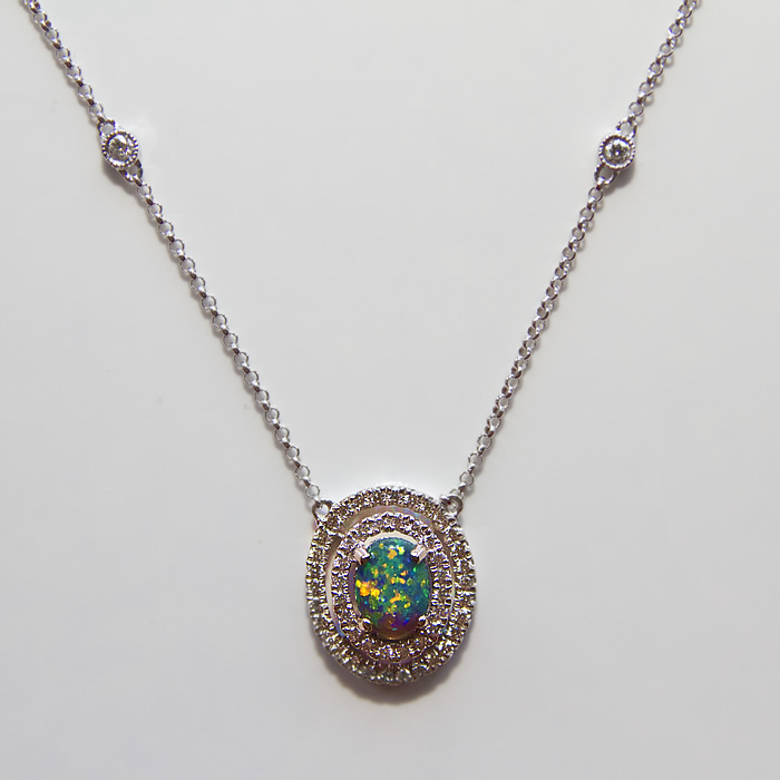 Black Opal set in a diamond double halo designed necklace. 0.44 carat Black Opal is accented by 0.33 carats of fine white brilliant cut diamonds set in 18k white gold.