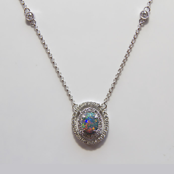 Black Opal set in a diamond double halo designed necklace. 0.39 carat Black Opal is accented by 0.44 carats of fine white round brilliant cut diamonds, set in 18k white gold.