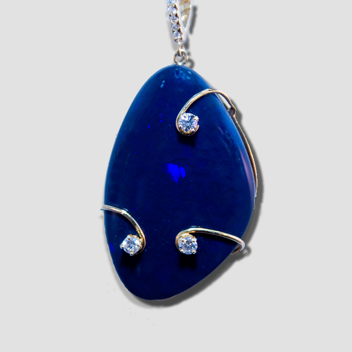 Free form dark blue with hints of red black opal, set in John's famous three stone diamond cradle