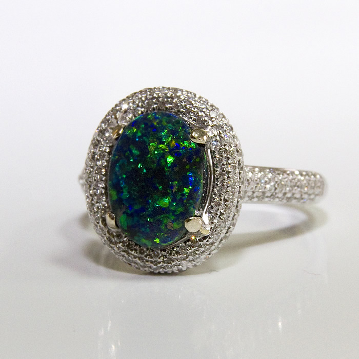John's classic design on steroids. This dazzling black opal and diamond ring features a 1.71 blue/green Black Opal accented with (219) fine white brilliant cut diamonds weighing .65 carats set in 18 karat white gold