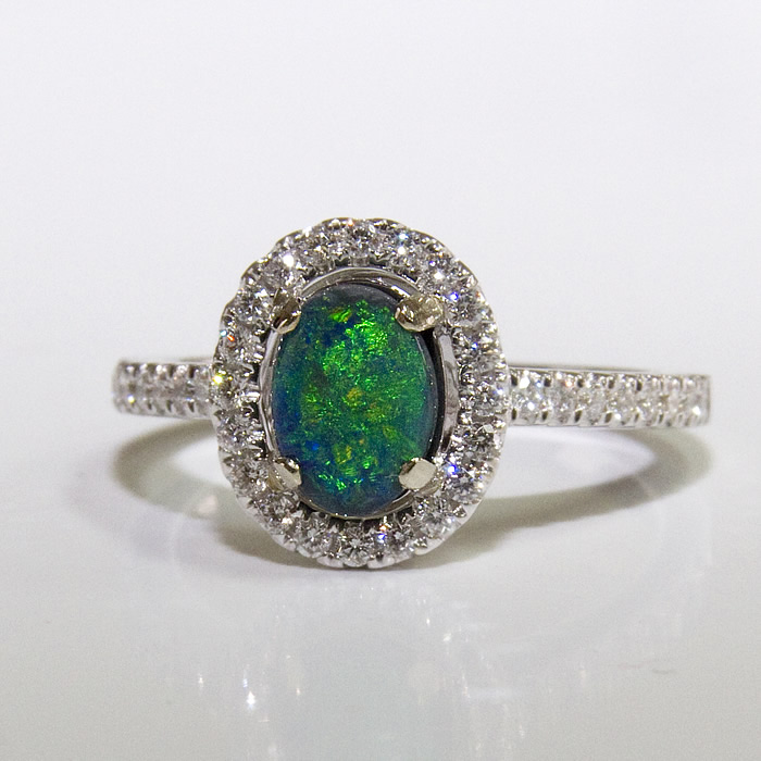 Classic beauty is what this ring has. A .77 carat black opal shines bright set in 18 karat white gold and surrounded by .36 carats of white diamonds