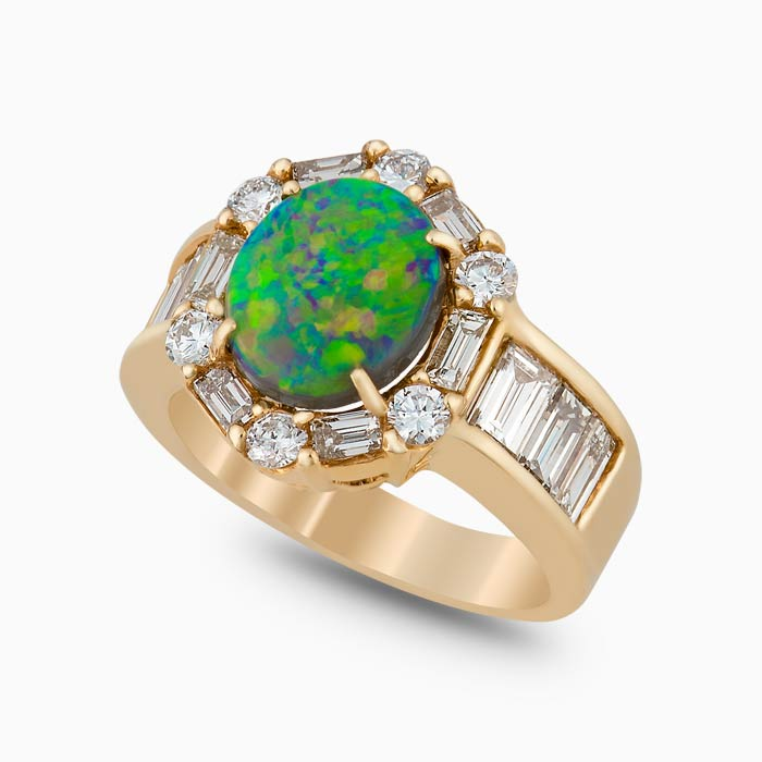 contoured ring has a black opal center stone that is 1.41 carats and encircled by 1.81 carats of gorgeous round and baguette diamonds. Set in 18 karat yellow gold