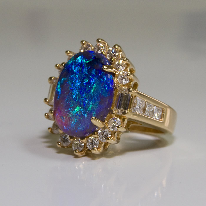 Black Opal Ring, 9.3O-cts embraced with .11cts Diamonds in a 14 karat gold setting