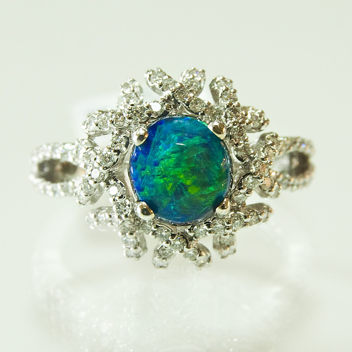 regal black opal ring features a 1.34ct center stone raised atop a beautiful love knot containing .75cts of diamonds and set in 18 karat white gold