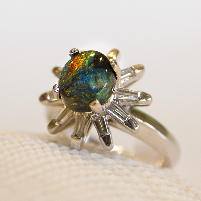 Black opal ring featuring .75cts of baguette diamonds surrounding a fiery 1.73ct black opal center stone