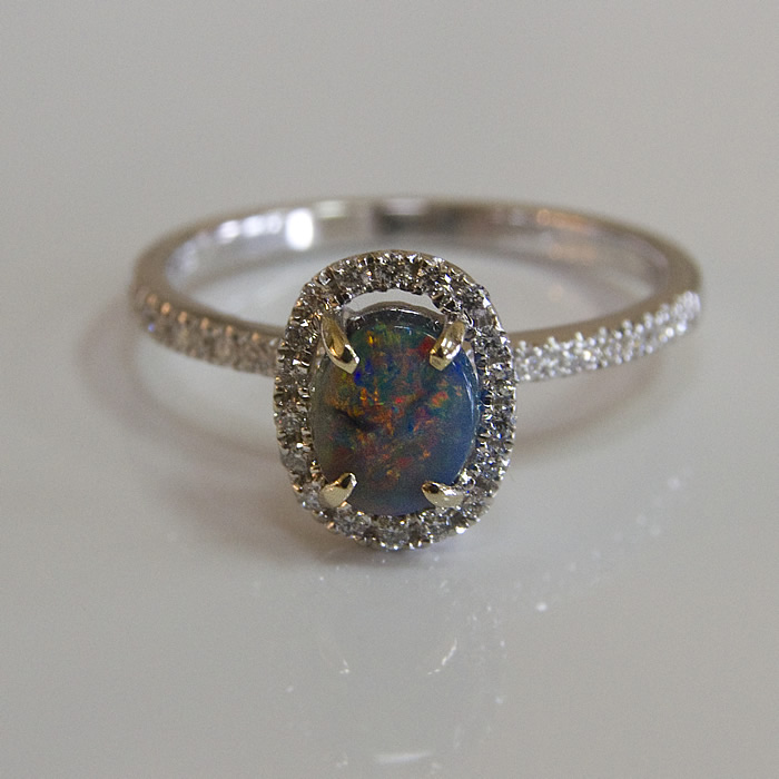 Beautiful black opal is surrounded by .22cts of diamonds and set in 18 karat white gold