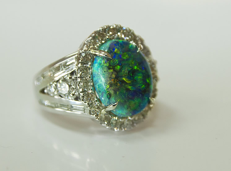 Lightning Ridge black opal weighing 5.76 carats accented by 2.44 carats of round and baguette diamonds set in platinum.